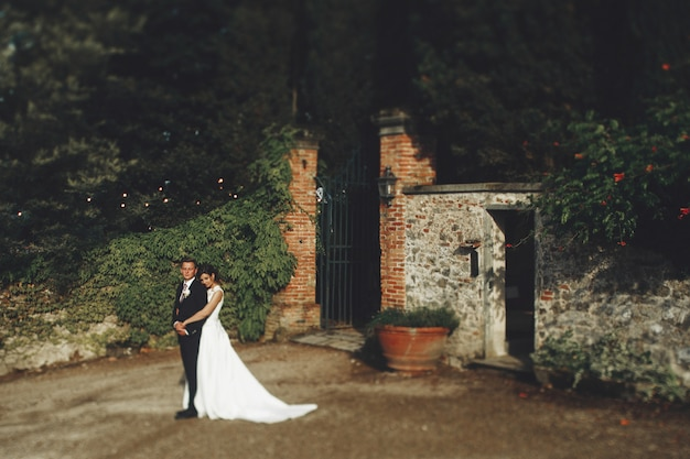 Lovely hugging wedding couple stands before the gates to an old italian villa