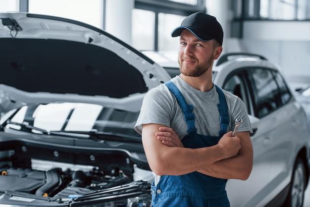 Прекрасная работа. сотрудник в синей форме стоит в автомобильном салоне