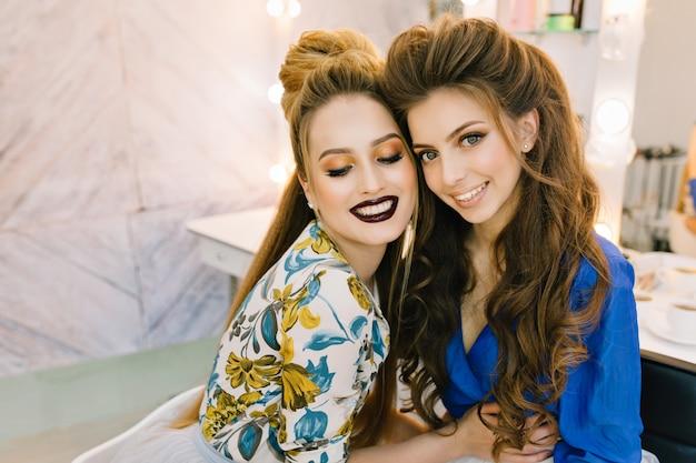 Belle gioiose graziose due giovani donne che abbracciano, divertendosi nel salone di parrucchiere