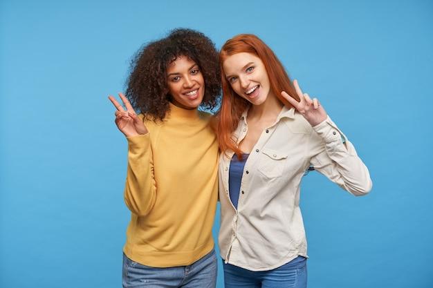 勝利のジェスチャーで手を上げて、青い壁に隔離された広い楽しい笑顔で喜んで見ている素敵な楽しい女性