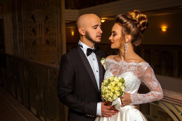 ファッショナブルな結婚式のスーツを抱き締める素敵なちょうど夫婦
