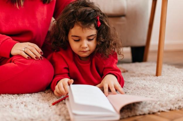 Прекрасный ребенок, рисунок в записной книжке. милая маленькая девочка, лежа на ковре.