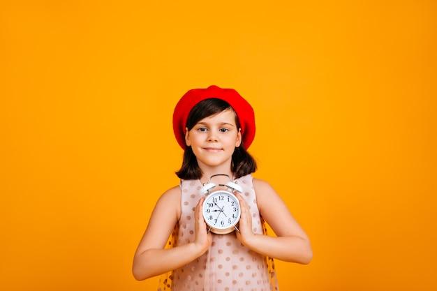 Прекрасный ребенок, держащий большие часы. восторженный кавказский ребенок, изолированные на желтой стене.