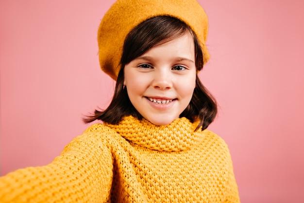 셀카를 만드는 사랑스러운 아이. 검은 머리 어린 소녀.
