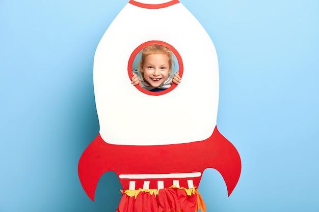 Un bambino adorabile posa dietro un grande razzo di carta