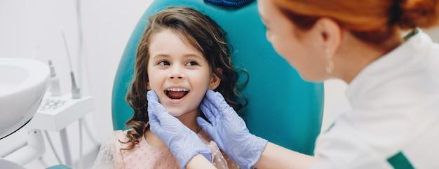 口腔病学で歯の手術を受けている間、医者に微笑んでいる素敵な子供