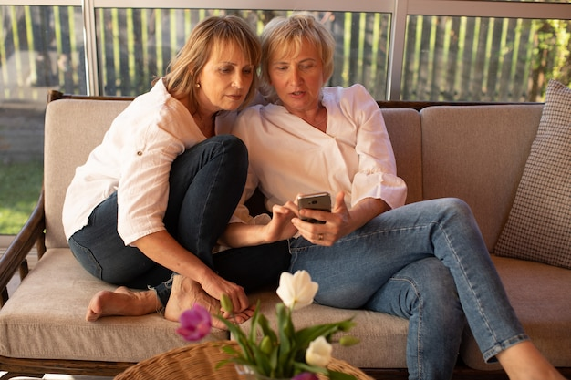 Lovely ladies 55 years old use smartphone while sitting on a sofa at table