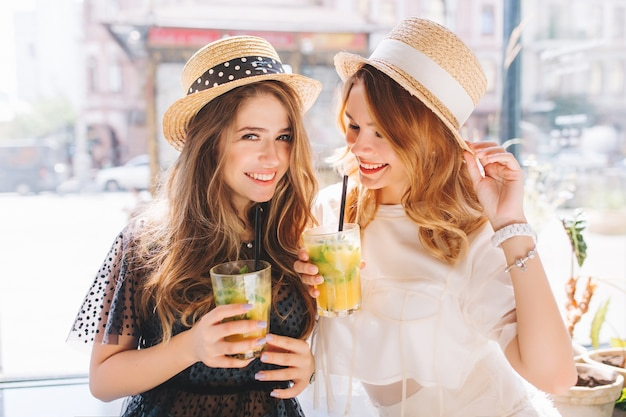 Lovely ladies wears similar straw hats having fun together enjoying icy fruit cocktails in summer day