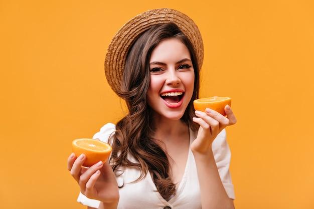 흰색 티셔츠와 밀짚 모자를 입은 사랑스러운 아가씨는 미소로 카메라를 바라보고 오렌지 조각을 보유하고 있습니다.