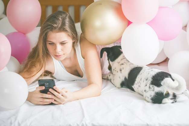Lovely lady in pajama making selfie in her bedroom using phone and hanging out with her dog.