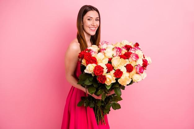 Милая дама позирует у розовой стены с букетом разноцветных роз