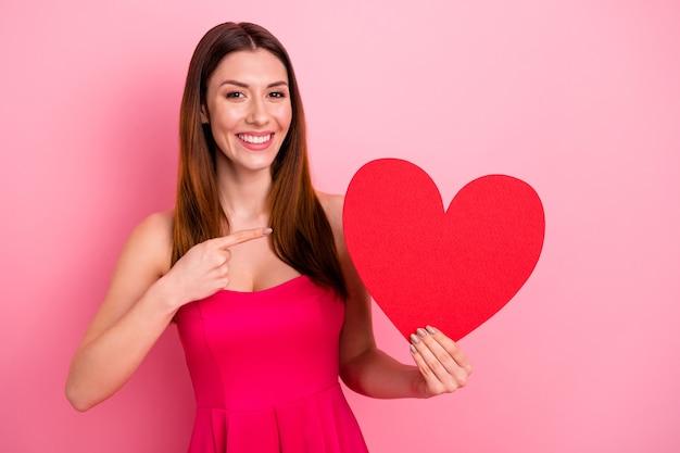 Милая дама позирует у розовой стены с красным сердцем