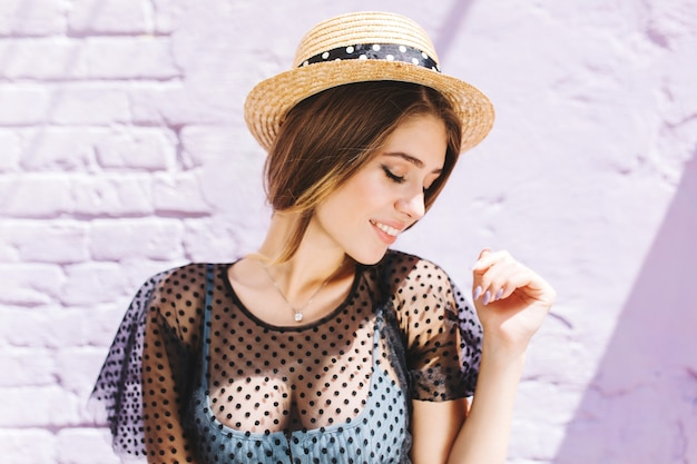 Lovely lady wears vintage hat and silver necklace looking away while posing near old white wall
