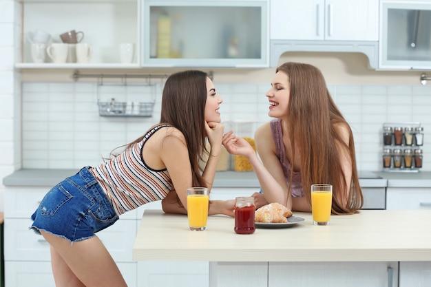 軽いキッチンで一緒に朝食をとる素敵なレズビアンのカップル