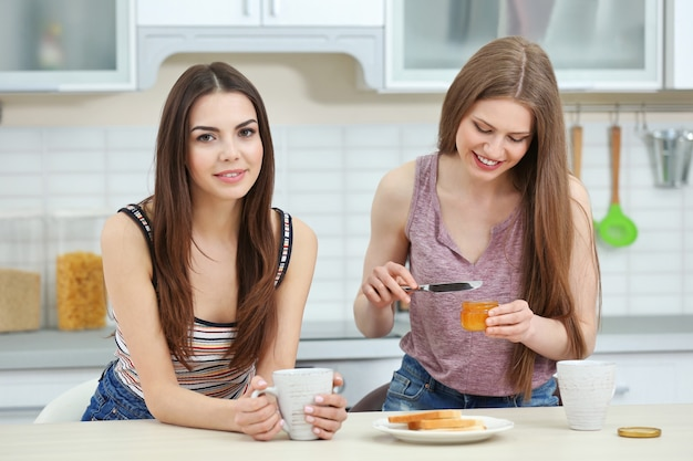 Lovely lesbian couple having breakfast together in light kitchen