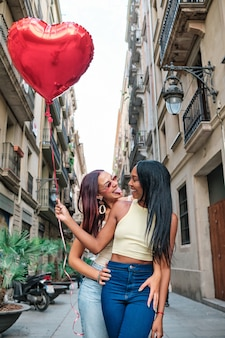 사랑스러운 레즈비언 커플은 거리에 서서 빨간 하트 모양의 풍선을 들고 서로를 바라보고 있습니다. lgbt와 발렌타인 데이 컨셉입니다.
