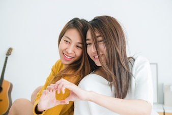Lovely lesbian couple together concept. couple of smiling young women sitting on the bed