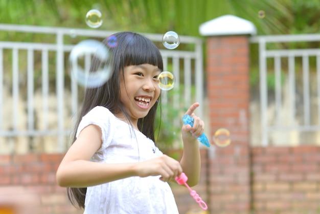Lovely little asian girl blowing soap bubbles, outdoor portrait.