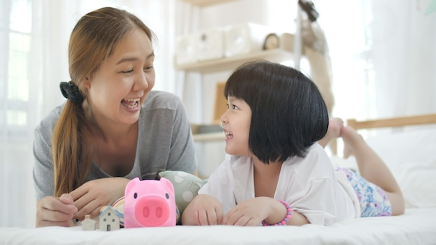 Lovely little asian girl and mother putting money in piggy bank for saving