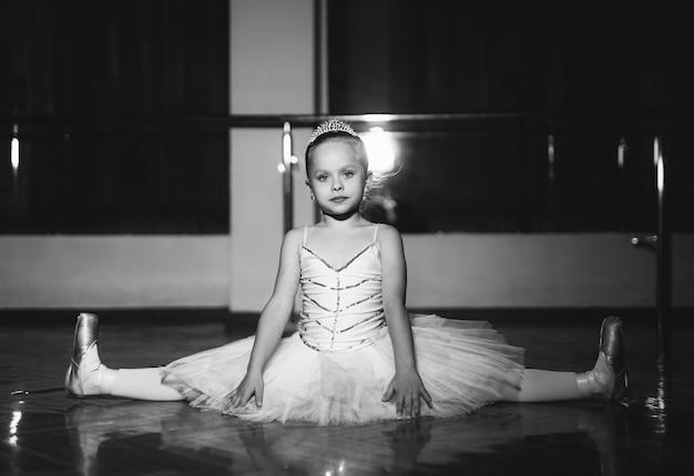 Милая маленькая балерина в белой пачке делает шпагат на фоне студии