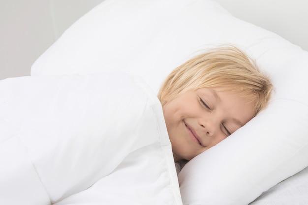 Милый маленький мальчик мирно спит в постели, улыбаясь, видя сон