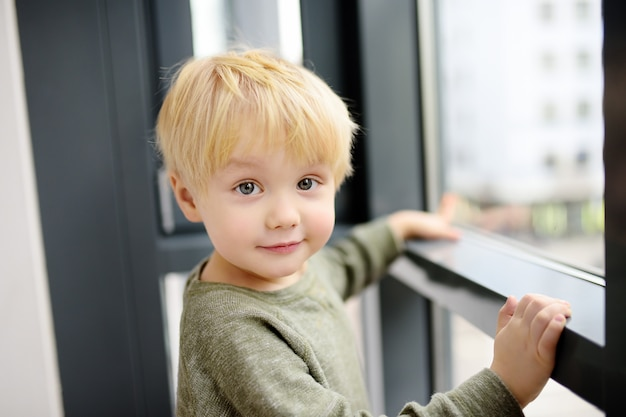 Lovely little boy sitting on the window near panoramic window and looking outside