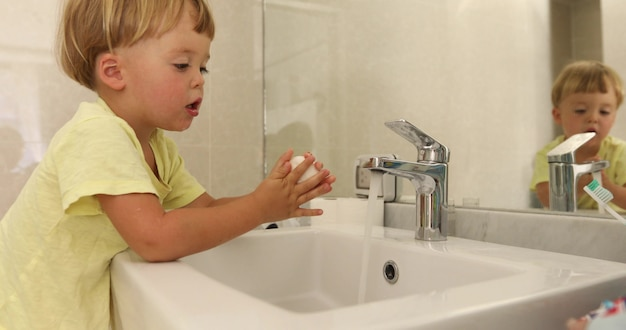 Lovely little boy using soap to wash hands over sink near mirror in stylish bathroom