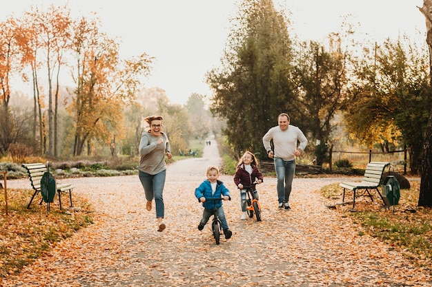 Милые младшие брат и сестра катаются на велосипедах, пока их родители бегают за ними, смеясь, в парке.