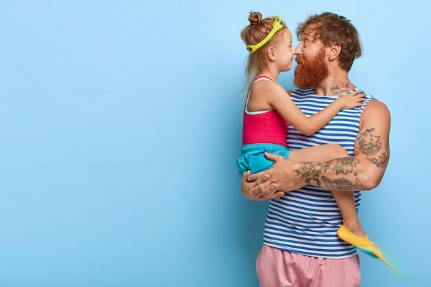 素敵な小さな子供と彼女の父親は鼻に触れ、一緒に時間を過ごし、女の子はゴーグルとフィンを着用し、パパと一緒に泳ぎたい、同じ趣味を持ち、空白のある青い壁に立ちます。家族の概念