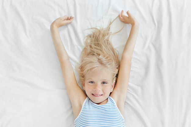 Lovely little child with blue eyes and freckles stretching in bed in morning, looking joyfully, enjoying relaxation and wanting to start new day.