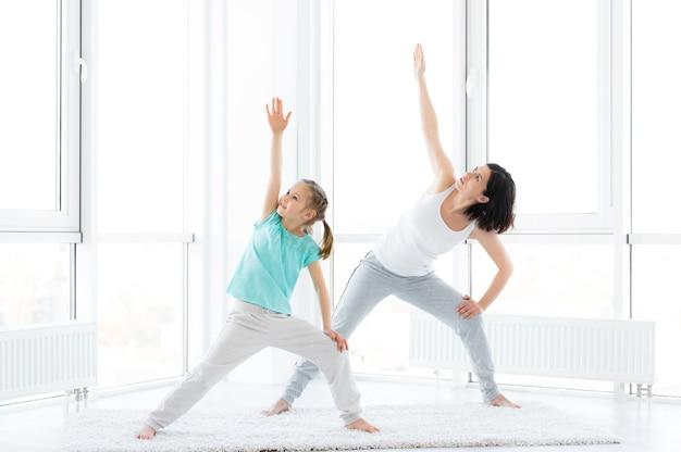 집에서 운동을 하는 사랑스러운 어린 소녀와 예쁜 여자