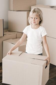 판지 상자를 들고 사랑스러운 어린 소녀