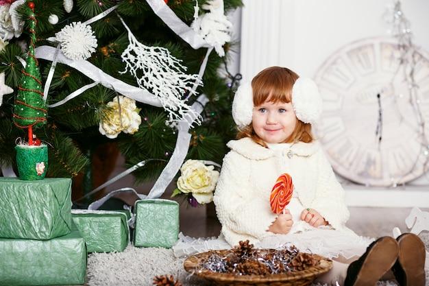 Милая маленькая девочка ест леденец на палочке. портрет забавной маленькой девочки в наушниках с вкусной конфетой в руках. рождество и новый год концепция