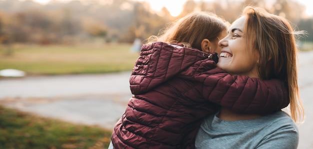 Милая маленькая девочка обнимает свою мать, пока мать смеется и держит за руки его дочь против заката на открытом воздухе.