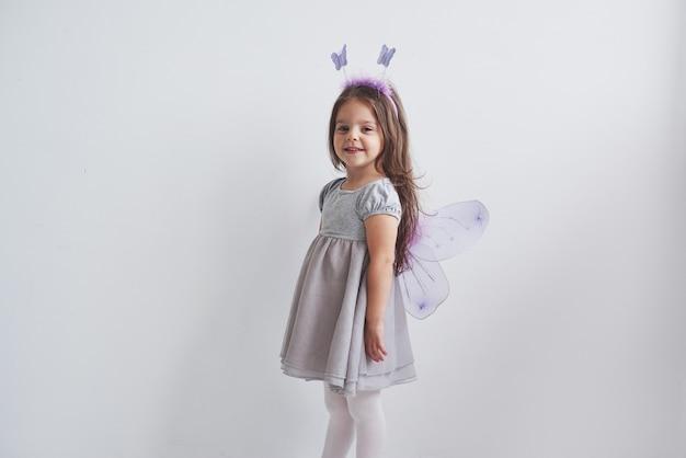 Lovely little girl in the fairy costume standing in room.