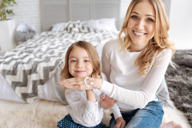 웃는 얼굴로 그녀의 어머니의 손을 잡고 사랑스러운 어린 소녀는 그녀의 어머니가 행복하고 웃고있는 동안 크림으로 그 위에 그렸습니다.