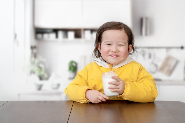 Lovely little girl is having breakfast and drinking yogurt with a spoon