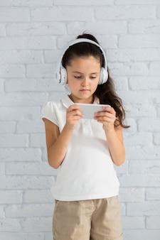Lovely little girl listening music with earphones