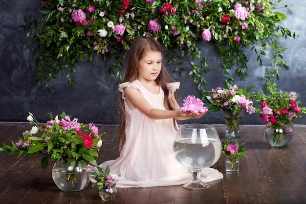 꽃병에 꽃의 꽃다발을 가지고 노는 사랑스러운 어린 소녀