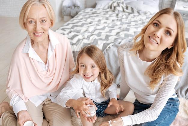 할머니의 손바닥에 서있는 크림 항아리에 손가락을 넣고 어머니의 손에 더 많은 크림을 바를 준비가 된 사랑스러운 어린 소녀