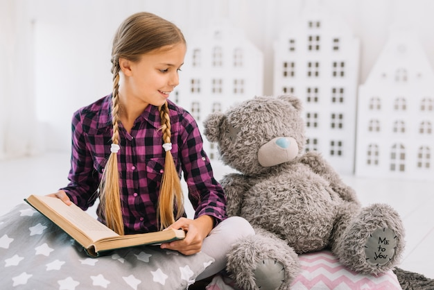 Lovely little girl reading a book with her teddy bear
