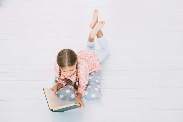 Lovely little girl reading a book