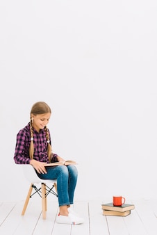Lovely little girl sitting on a chair reading a book
