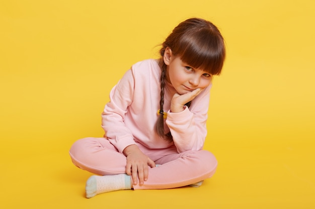 Lovely little girl sitting on floor with crossed legs, keeping palm on chin, looking bored at camera, female child wearing rosy casual attire, kid wants playing, does not know what to do.