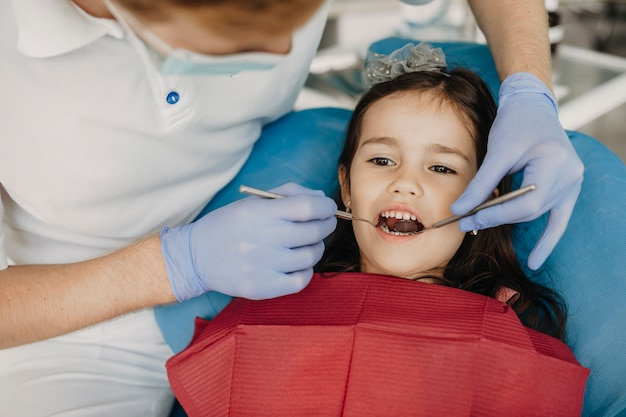 소아 치과 의사에 의해 치아 검사를 갖는 구강 좌석에 앉아 사랑스러운 어린 소녀.