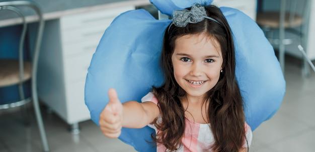 歯の手術を受けた後、笑いながら親指を立てて、口腔病学の椅子に座っている素敵な女の子。