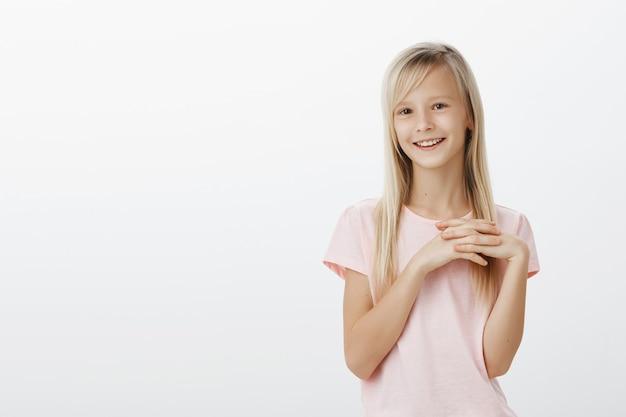 Милая маленькая девочка улыбается и выглядит тронутой