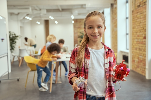 사랑스러운 어린 소녀가 카메라를 보고 웃고 교실에 서 있는 동안 diy 로봇을 보여줍니다.