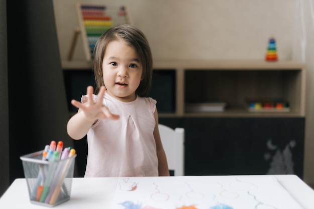 Lovely little girl stands by the table behind which she is painting on paper