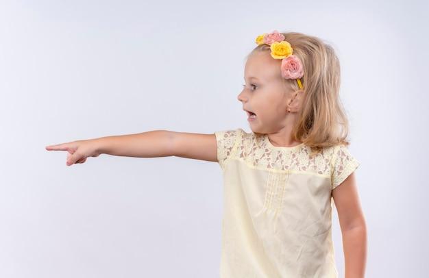 Una bambina adorabile che indossa la camicia gialla nella fascia floreale che indica il lato con il dito indice su una parete bianca